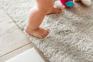 baby s standing on gray floor rug